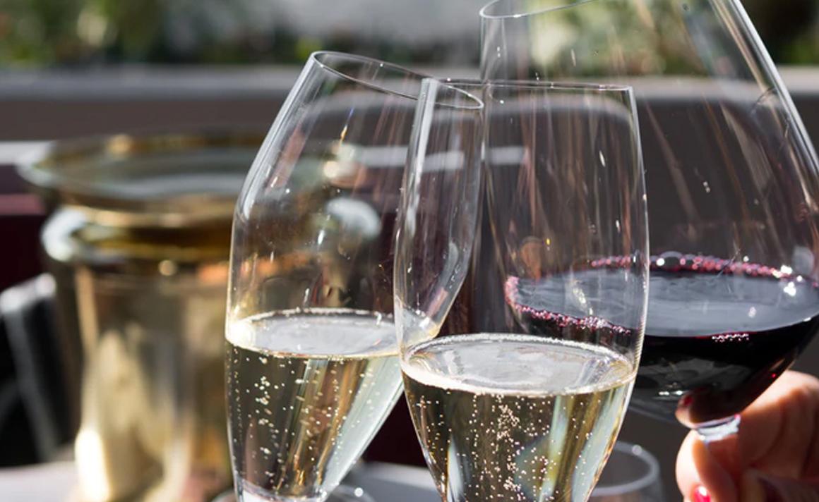 2 glazen champagne klinken met een glas rode wijn